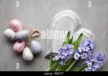 Ostern flach mit blauen Hyazinthen Blumen, Ostereier und großen Herz auf hellem Stein Hintergrund