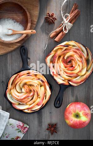 Hausgemachte Blätterteig mit Rose geformte Apfelspalten gebacken in Eisen skillets. Top lag auf Holzbrett mit einigen Äpfeln und Zucker - Stockfoto