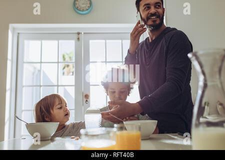Vater der seine Kinder zu Hause und das Büro auf Handy. Mann am Frühstückstisch mit seinen Kindern. - Stockfoto