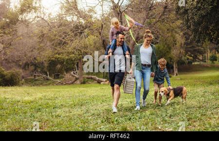 Glückliches Paar mit ihren zwei Kindern und Hund Wandern im Park. Mann, der kleine Mädchen mit Drachen auf Schultern und Frau, die einen Picknickkorb mit - Stockfoto