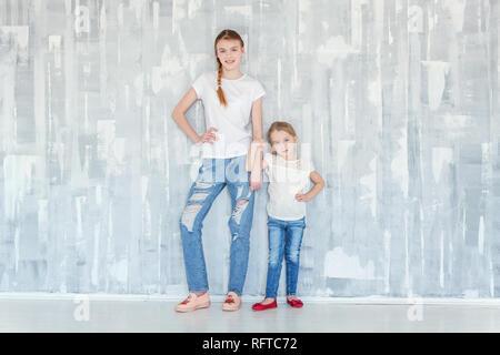 Zwei glückliche Kinder gegen Grau texturierte Wand Hintergrund und umarmt. Adorable hübsches kleines Mädchen umarmt fest Süßes junges Mädchen, zeigte ihr - Stockfoto