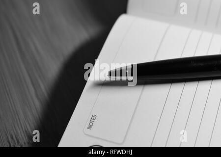 Ein Stift auf einem Notebook - Stockfoto