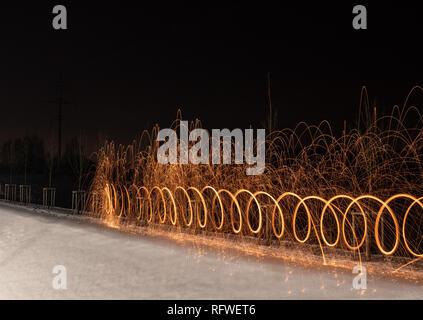 Licht malerei Kunst Spinning Stahlwolle in abstrakten Kreis, Feuerwerk Duschen von hellen gelb leuchtenden Funkeln im Winter verschneite Tal. - Stockfoto