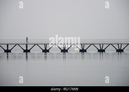 Einsamer Mann auf einer Brücke über Wasser in Lissabon, neblige Atmosphäre, Copyspace - Stockfoto