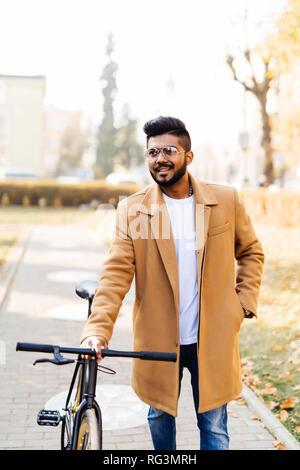 Junge hipster style Mann posiert mit dem Fahrrad auf die Straße für die Reise bereit - Stockfoto