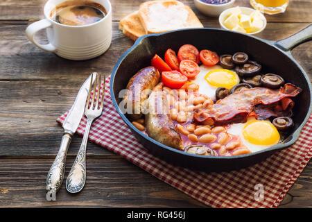 Gebratene Eier, Würstchen, Speck, Bohnen und Champignons in Iron Skillet, Toast, Kaffee, Butter und Marmelade auch an rustikalen Holzmöbeln Hintergrund. Englisches Frühstück.