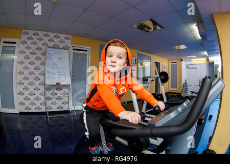 29. Januar 2017. Ukraine, Kiew. Thema Kind geht. Kaukasische Baby 3 Jahre tun cardio Training, Aufwärmphase Muskeln auf Fahrrad Simulator in g - Stockfoto