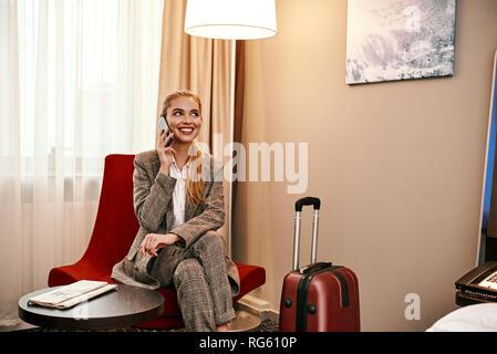 Wichtiger Anruf. Junge und stilvolle Geschäftsfrau mit Koffer und Smartphone sitzt auf einem Sofa im Hotel Zimmer - Stockfoto