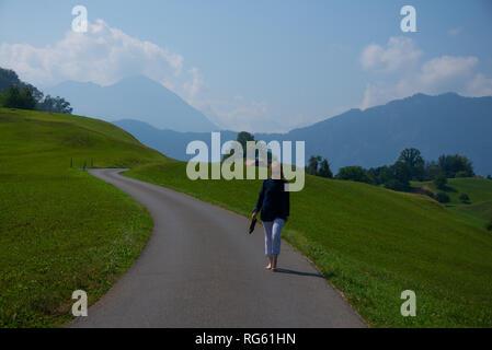 Frau barfuß entlang einer Straße, Schweiz - Stockfoto