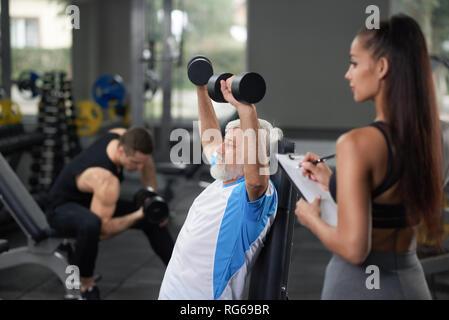 Horisontal Detailansicht von drei Leuten im Fitnesscenter zu trainieren. Athletische junge Frau stehen und weg schauen mit Tablette, während Ihr Client elderler Mann tun, ausüben. Konzept des Lebensstils. - Stockfoto