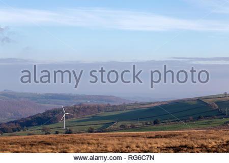 Einzelne große weiße Windenergieanlage in offenen englischen Landschaft mit sanften Hügeln und blauer Himmel - Stockfoto