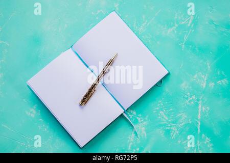 Öffnen Notebook mit einem Gold pen auf azurblauem Hintergrund der Ansicht von oben, Büro Schreibtisch flach. Schule notebook Tisch. Tagebuch Buch für Planer ihr Leben. Design - Stockfoto
