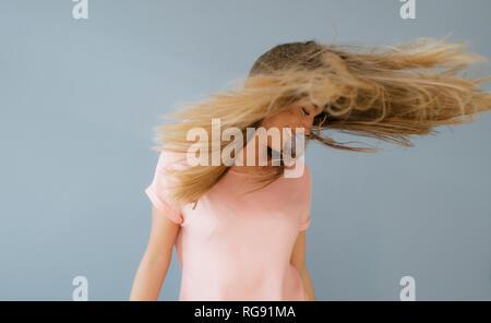 Lachende junge Frau ihr Haar werfen