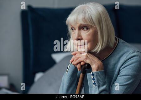 Nachdenklich ältere Frau mit Händen auf Gehstock sitzen auf dem Bett zu Hause.