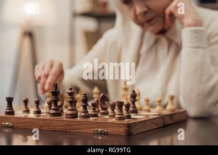 7/8-Ansicht der älteren Frau am Tisch sitzend, propping Kinn mit der Hand und Schach spielen zu Hause