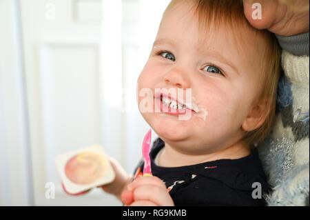 Kleinkind weiblichen von knapp über zwei Jahre alt, haben Spaß, der in ein Durcheinander essen einen Joghurt Foto aufgenommen von Simon Dack