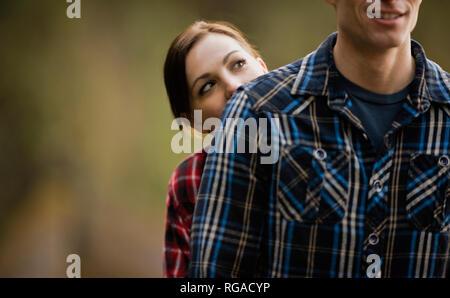 Frau versteckt sich hinter Freund tragen Plaid Shirt. - Stockfoto