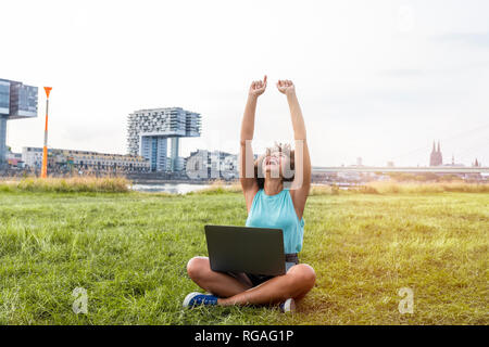 Deutschland, Köln, jubeln Frau sitzt auf einer Wiese mit Laptop - Stockfoto
