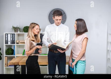 Thema business, Teamwork und Partnerschaften. Eine Gruppe von jungen Menschen, drei Personen, stand in einem Büro in der Nähe des Tisches in der offiziellen Kleidung, Arbeit mit Doc - Stockfoto
