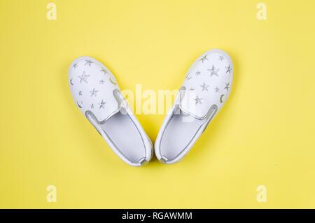 Frauen oder junge Mode, weiss slipons, stilvolle Schuhe auf gelben Hintergrund. Mode und Schönheit Konzept. Flach, Ansicht von oben kopieren. - Stockfoto