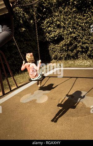 Zwei Latina Mädchen, auf Schaukeln in einem Park auf einem Spielplatz und Schatten - Stockfoto