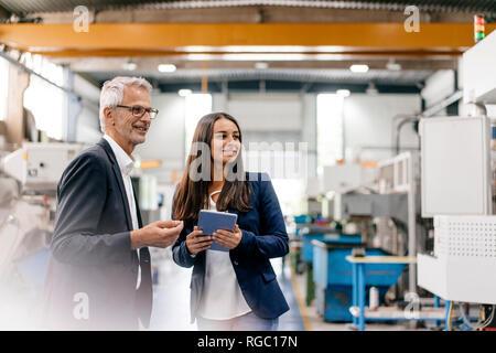 Geschäftsmann eine Frau in High Tech Unternehmen, ein Treffen in der Werkhalle - Stockfoto