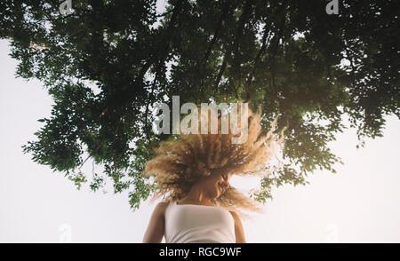 Junge Frau mit blonden Korkenzieherlocken stylen ihr Haar werfen