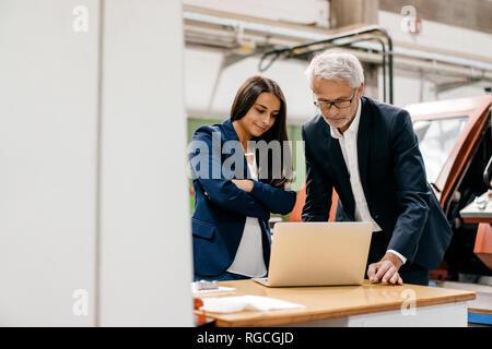 Geschäftsmann eine Frau in High Tech Unternehmen, in einer Sitzung, mit Laptop - Stockfoto