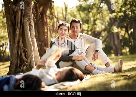 Zwei asiatische Kinder Jungen und Mädchen Spaß haben liegen auf Gras, ein Buch zu lesen mit den Eltern sitzen gerade im Hintergrund, auf dem Eltern in b Fokus Stockfoto