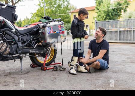 Gerne Vater und Sohn neben einem Motorrad - Stockfoto