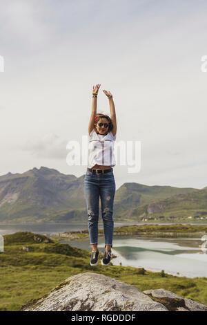 Junge Frau auf einem Felsen, Lappland, Norwegen springen - Stockfoto