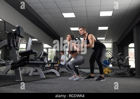 Passende Frau hockt und Barbell anheben, während Sie im Fitnessraum. Muskulöse Trainer unterstützen und helfen, Brünette. Sportlicher Mann und Frau tragen in Sportkleidung und Turnschuhe. - Stockfoto
