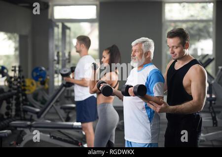 Indoor Porträt von Menschen, die bei der täglichen Training in der Turnhalle. Ältere Menschen fit zu bleiben und das Training mit freien Gewichten mit Hilfe von jungen professionellen Trainer in schwarz Sportbekleidung. Andere Besucher Übungen. - Stockfoto