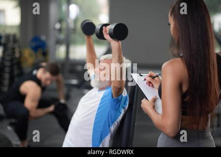 Closeup Erntegut Portrait von älteren Menschen während der täglichen geplante Training im Fitnessraum mit Trainer. Mann hält den Arm über den Kopf und Trainieren mit Gewichten, während junge sportliche konzentriert Frau schreiben auf Tablet. - Stockfoto