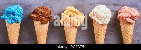 Panorama Banner mit verschiedenen Geschmacksrichtungen der handwerklichen Speiseeis Zucker Kegel in einer Reihe serviert auf einem Schiefer Hintergrund - Stockfoto