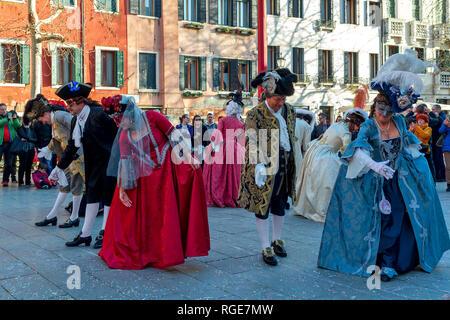 Gruppe von Menschen, die typischen Kostüme und Masken tanzen auf kleinen Platz während der berühmten traditionellen Karneval in Venedig. - Stockfoto
