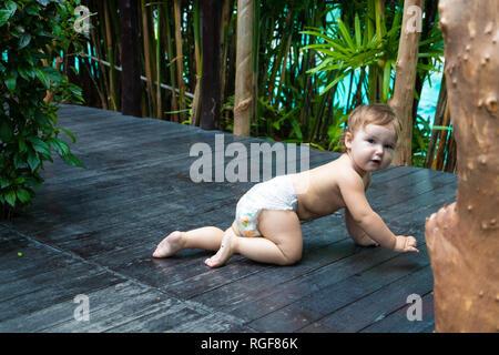 Hübsches Baby Mädchen lächelnd zu Kriechen und Krabbeln auf dem hölzernen braun Gehweg auf dem Hintergrund der grüne Büsche und Bäume. Das Kind auf den Boden und versuchen zu essen. Es ist ein Platz für Text. - Stockfoto