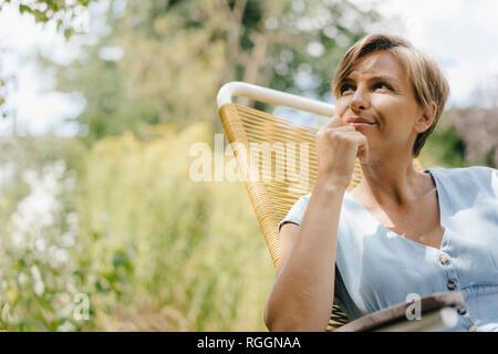 Portrait von Frau sitzt im Garten am Lehrstuhl - Stockfoto