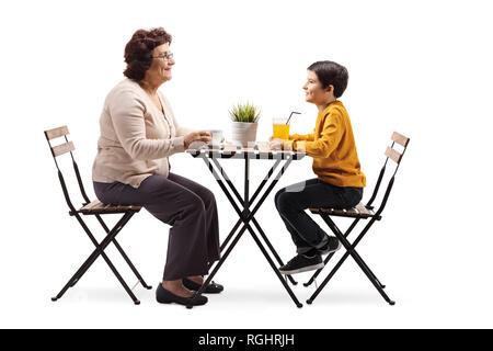 Die volle Länge der Großmutter an einem Tisch sitzt und spricht zu ihr Enkel auf weißem Hintergrund - Stockfoto