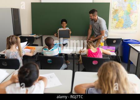 Vorderansicht des glücklichen Schüler holding Schiefer- und stehend an greenboard im Klassenzimmer der Volksschule - Stockfoto
