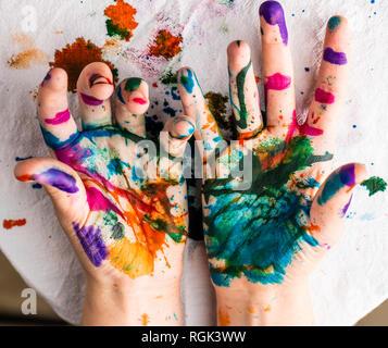 Die Hände des Kindes sind in Rot, Rosa, Gelb, Orange, Rot, Blau, Grün und lila Tinte. Konzepte: Kunst, Bildung, Spielen, Aquarell, Malen mit den Fingern - Stockfoto