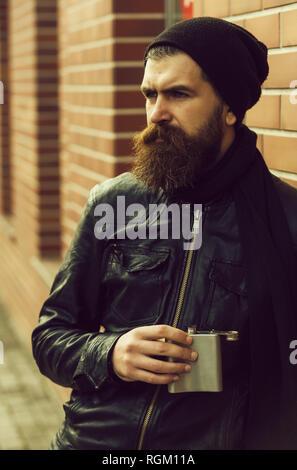 Ernsthafte bärtiger Mann Hipster mit metallischem Glas in Lederjacke - Stockfoto