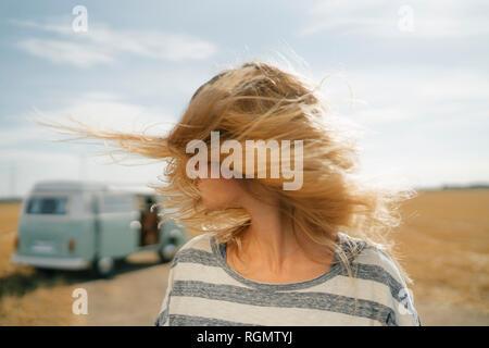 Blong junge Frau von Camper van in ländlichen Landschaft schütteln ihr Haar - Stockfoto