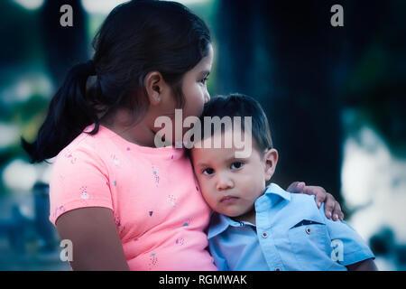 Eine emotional verletzte Junge lehnte sich auf ihre ältere Schwester und durch ihren Kuss und Support getröstet. - Stockfoto