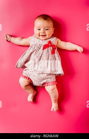 Portrait von Happy Baby Mädchen liegt auf rosa Hintergrund - Stockfoto