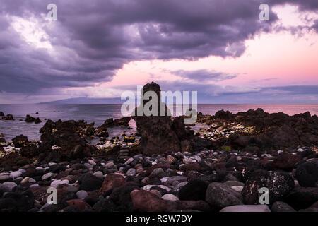 Blick nach Westen in Richtung der Insel La Gomera von einem Kieselstrand in Playa San Juan im Morgengrauen an einem bewölkten Tag, Teneriffa, Kanarische Inseln, Spanien - Stockfoto