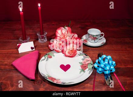 Florales Muster, feines Porzellan Geschirr mit passenden Teller, Tasse und Untertasse. Bouquet von Orange und Weiß rpses, rosa Serviette, Besteck, rote Kerzen und - Stockfoto