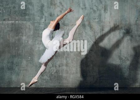 Springen Ballerina. Junge schöne Frau Ballett Tänzerin, in professionellen Outfit gekleidet, Spitzenschuhe und weißen Tutu.