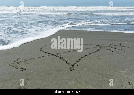 Eine Hand befinden Liebe Herz im Sand mit einem Pfeil durch it - Stockfoto
