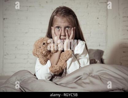 Angst kleines Mädchen im Bett sitzen, die ihr Gesicht mit den Händen ihren Teddy Holding in Angst Angst vor Monstern in der Dunkelheit im Schlafzimmer in Kind Alpträume - Stockfoto